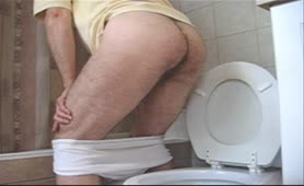 Skinny guy pooping a big one over toilet