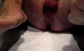 Hairy guy pooping on white napkin